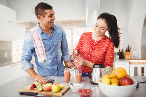 Smiling woman pouring fruit juice in glass with man talking to her stock photo