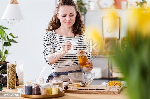 Smiling woman pouring honey into bowl with natural ingredients to make organic face cream