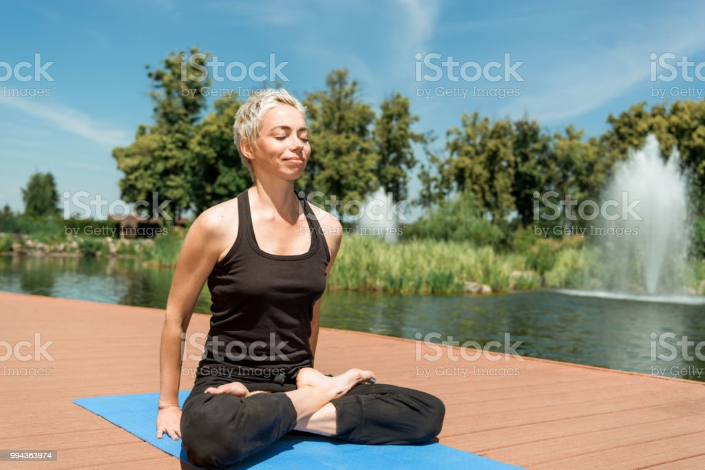 Smiling Woman Practicing Yoga In Lotus Pose On Yoga Mat Near River In Park Stock Photo Download Image Now Istock