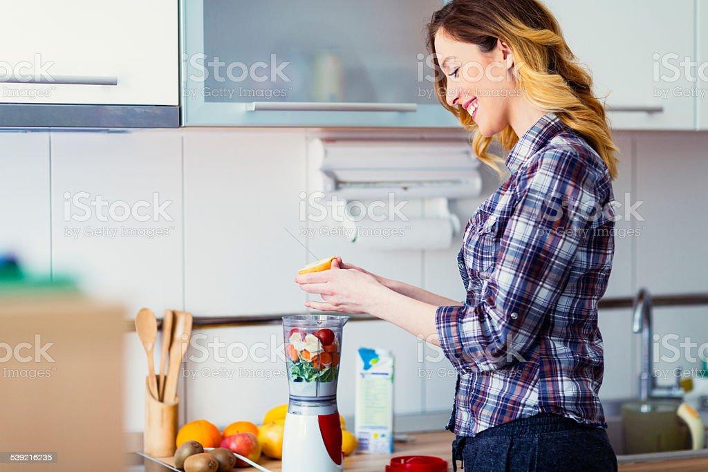 Smiling Woman Preparing Smoothies. stock photo