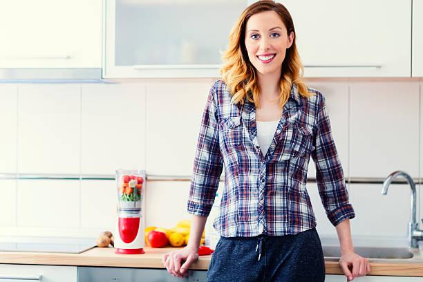 Souriant femme préparant des Smoothies. - Photo