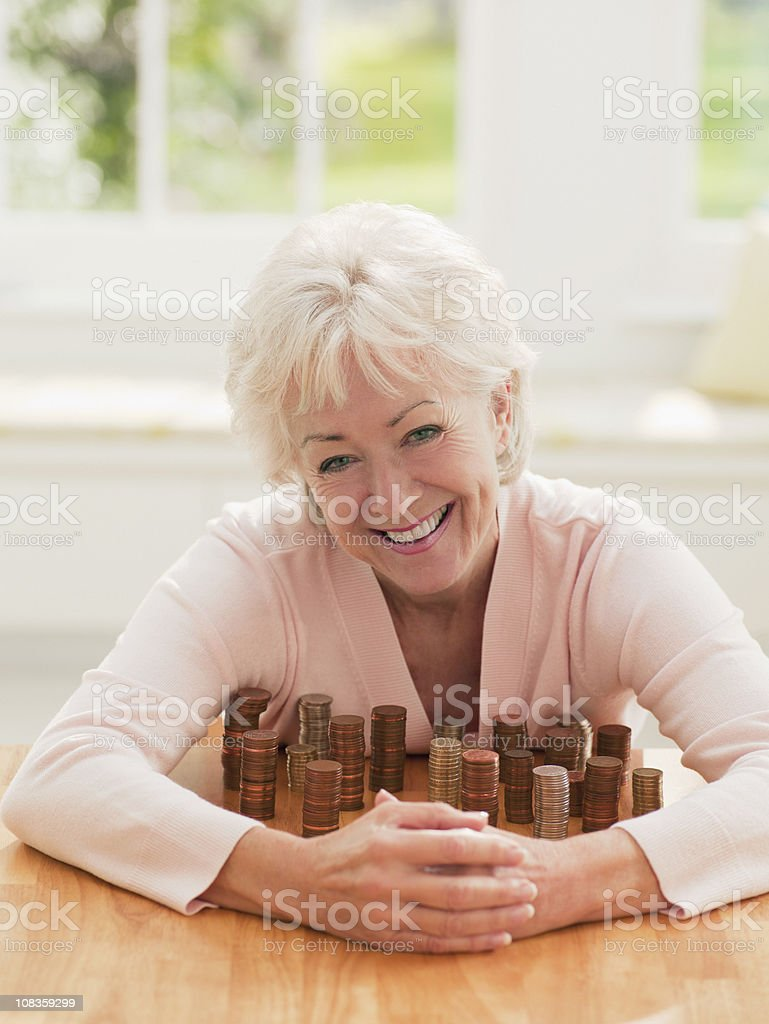 Smiling woman protecting stacks of coins stock photo