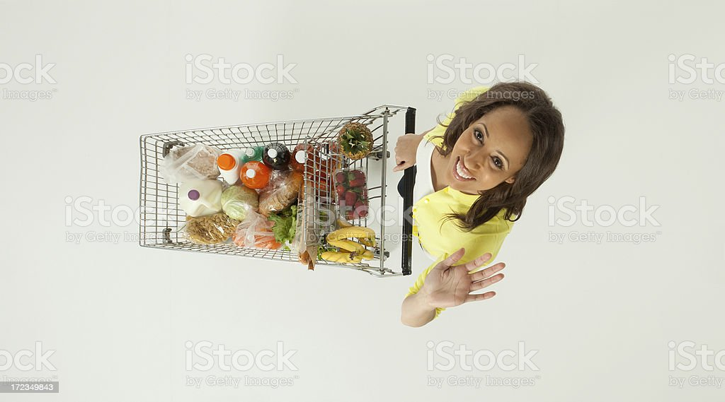 Smiling woman pushing a shopping cart and waving royalty-free stock photo