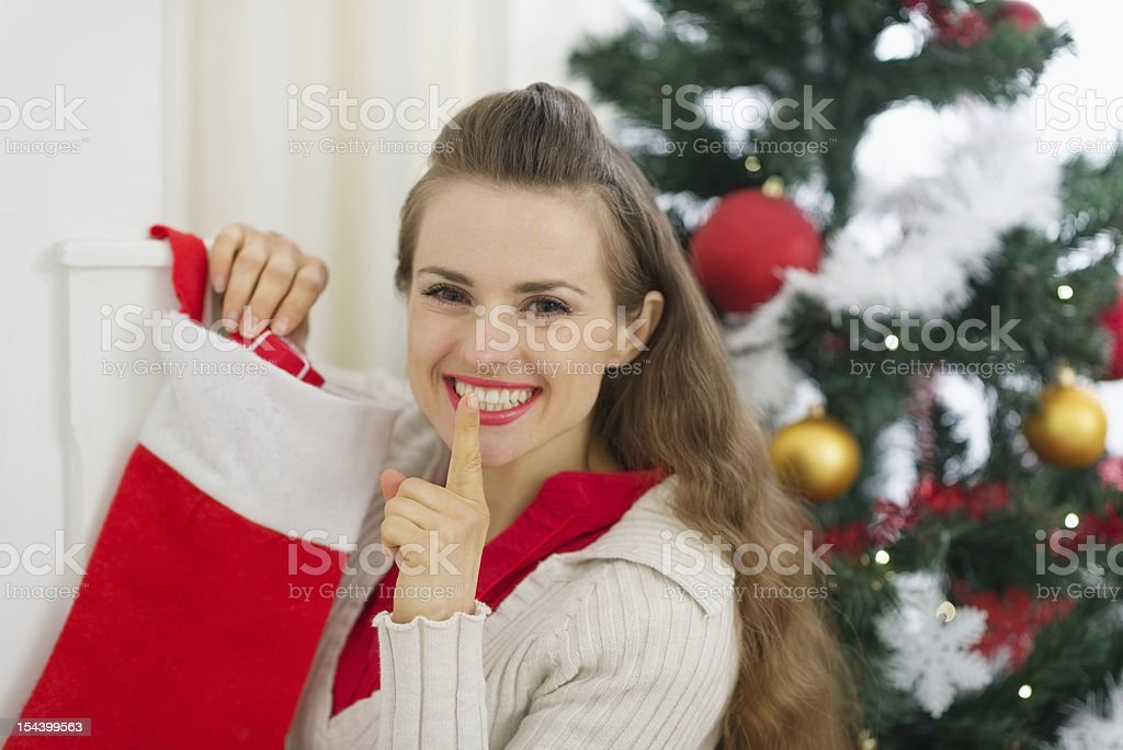 Smiling woman put gift in Christmas socks and showing shh stock photo