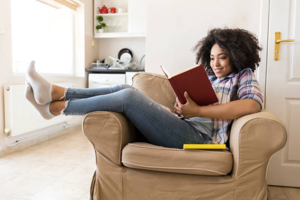 Smiling woman reading a book at home stock photo