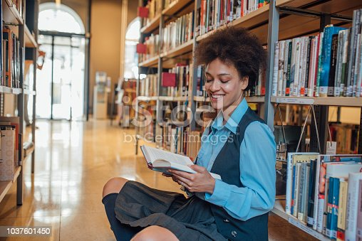 istock Smiling woman reading a book 1037601450