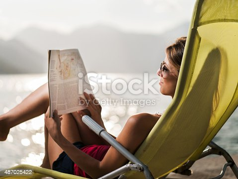 Young woman relaxing in deck chair at the seaside and reading a magazine.