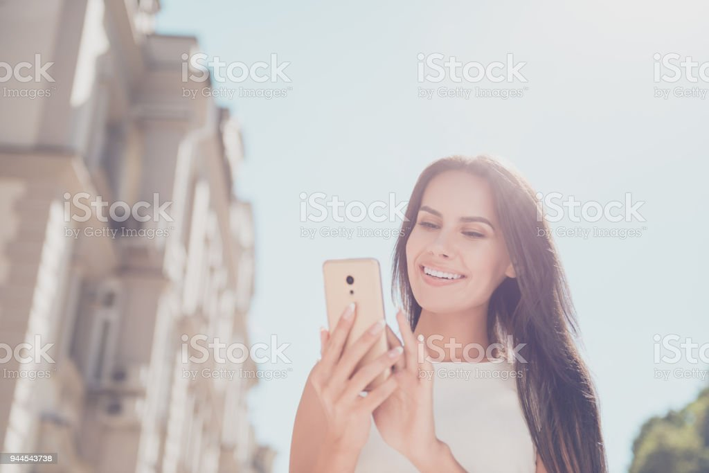 Smiling woman reading message on mobile phone while standing on the...