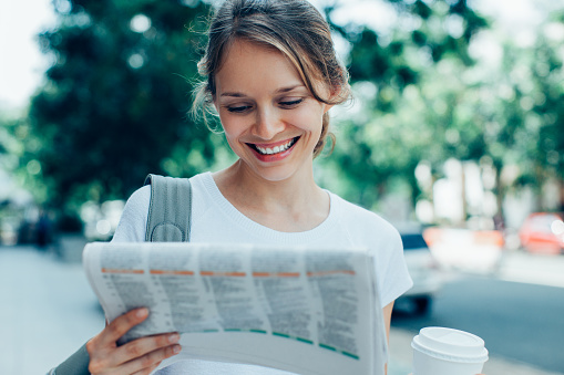 Smiling Woman Reading Newspaper on Street