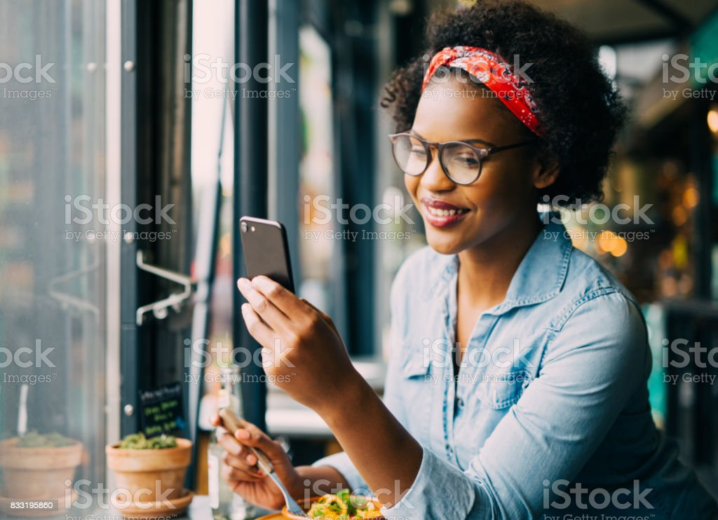 Smiling woman reading text messages over dinner in a bistro stock photo