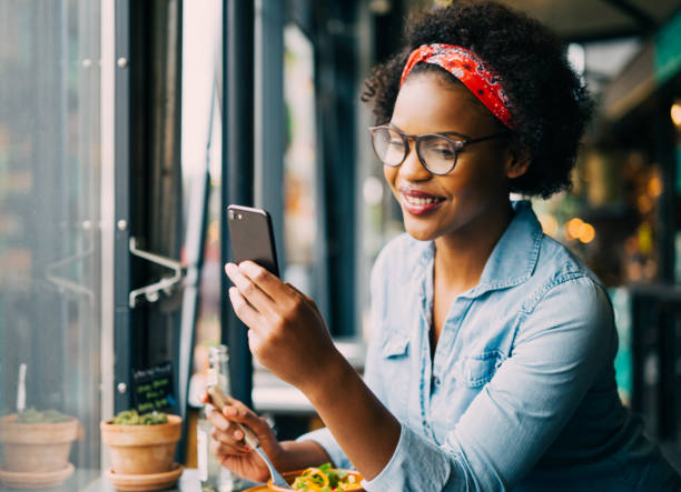 smiling woman reading text messages over dinner in a bistro - person using phone stock photos and pictures