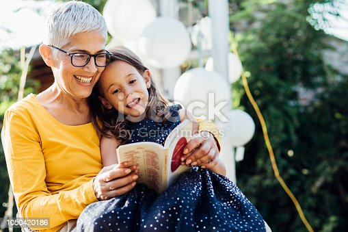 Old woman reading a book to her grandchild outdoors