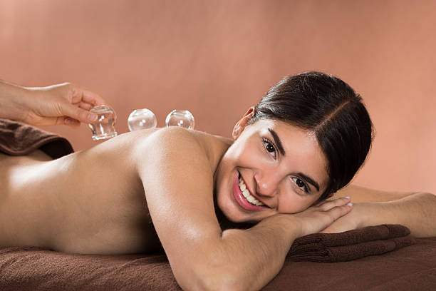 smiling woman receiving cupping therapy - cupping therapy stock photos and pictures