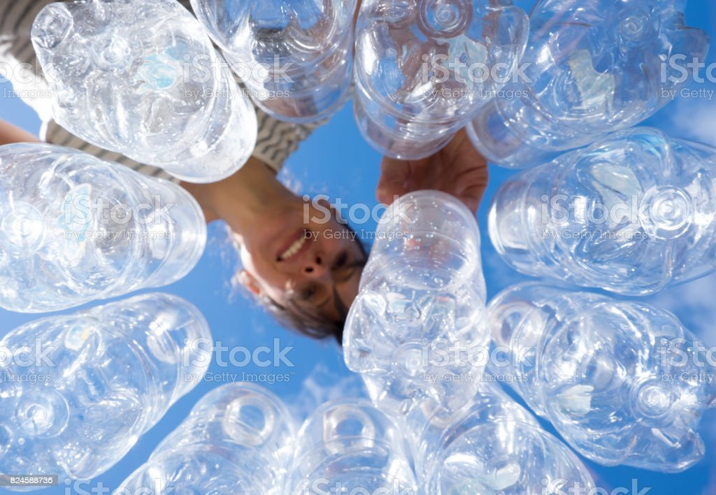 Smiling woman recycling plastic water bottles stock photo
