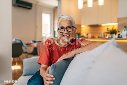 1044149594 istock photo Smiling woman relaxing at home 1169813086