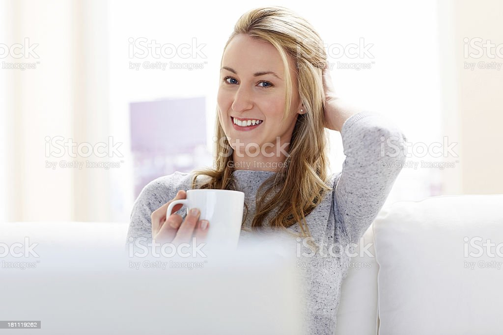 Smiling woman relaxing at home with a cup of coffee royalty-free stock photo