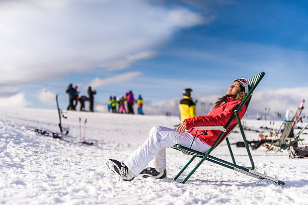 Smiling woman relaxing in deck chair at ski resort. stock photo