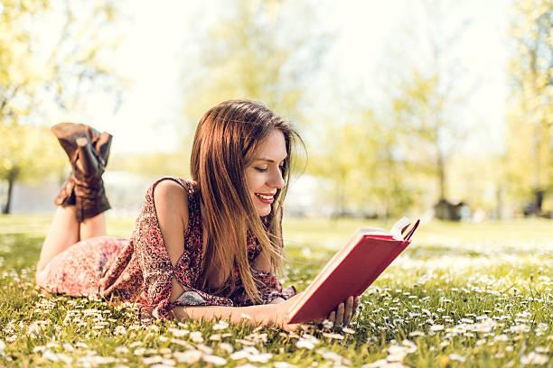 Lächelnde Frau entspannend auf Gras und Lesung Buch. – Foto