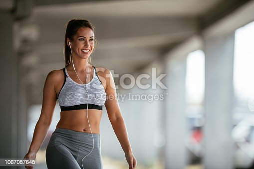 Smiling woman resting after workout. Shallow DOF. Developed from RAW; retouched with special care and attention; Small amount of grain added for best final impression. 16 bit Adobe RGB color profile.