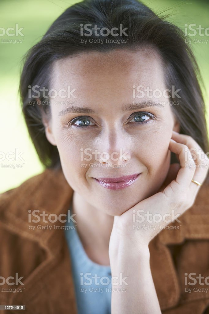 Smiling woman resting chin in hand stock photo