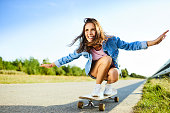 Smiling woman riding longboard in countryside during summer