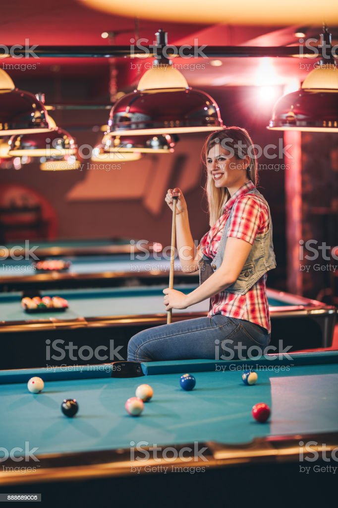 Young happy woman sitting on pool table and rubbing pool cue with a...