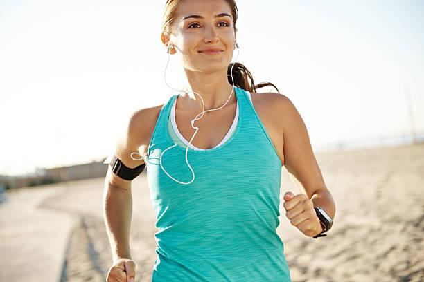 Una mujer sonriente corriendo mientras usando auriculares - foto de stock
