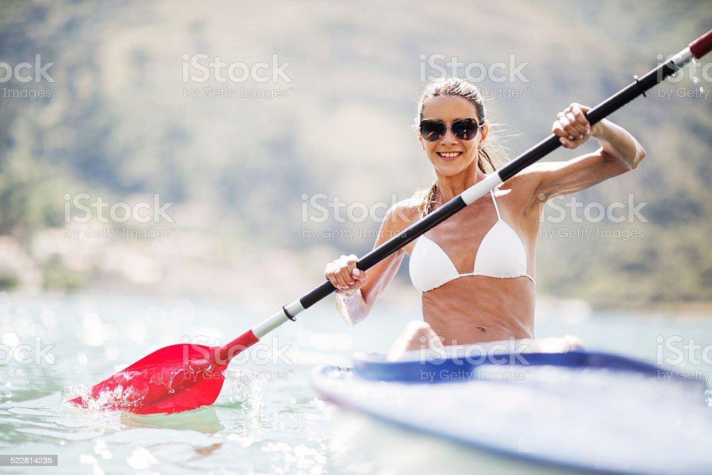 Smiling woman sea kayaking. stock photo