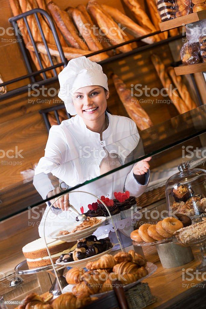 Mulher sorridente de venda de doces e pães frescos foto royalty-free
