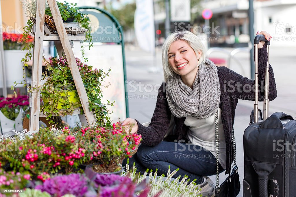 Smiling woman shopping flowers in the city stock photo