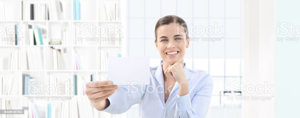 smiling woman showing business card in her hand on interior office background stock photo