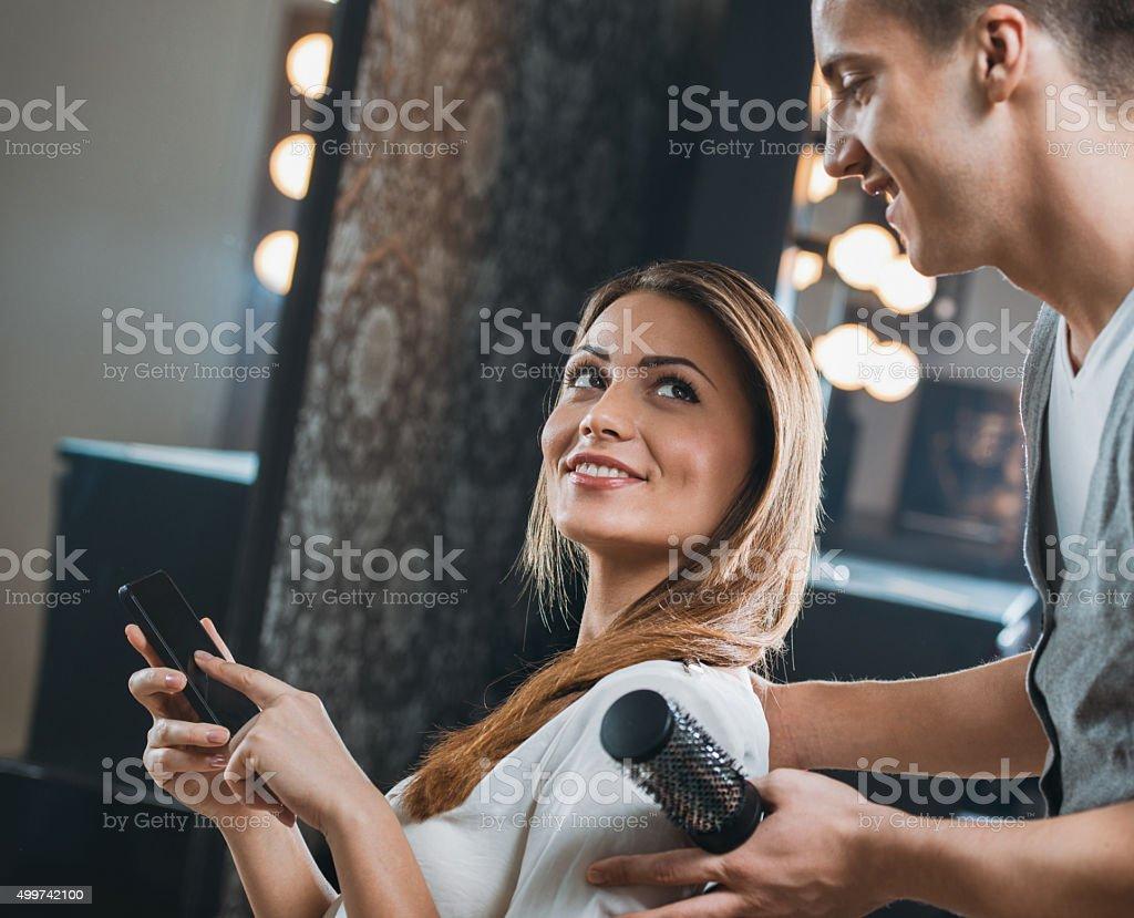 Mujer sonriente mostrando peluquería mensaje de texto en su teléfono celular - foto de stock