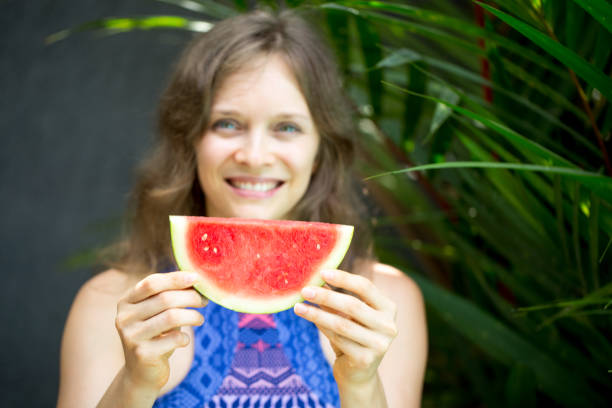 Smiling Woman Showing Slice of Watermelon stock photo