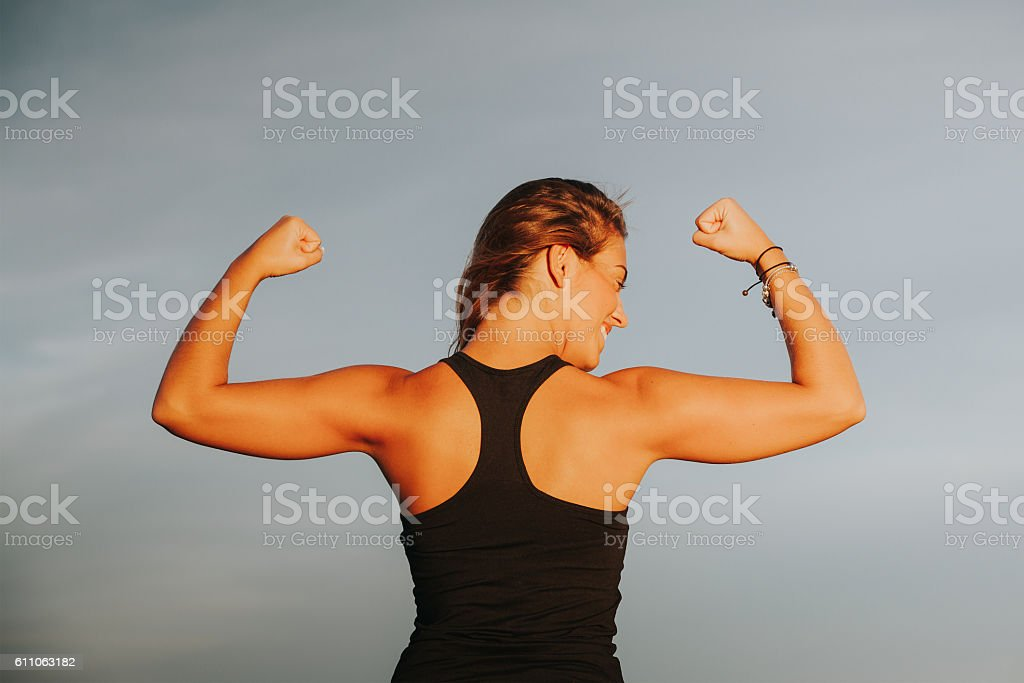 Smiling woman showing strong biceps after outdoors fitness workout. stock photo