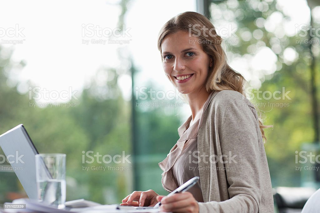 Smiling woman sitting at desk with paperwork stock photo