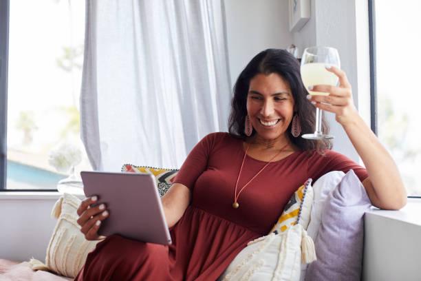 微笑的女人坐在家裡與朋友通過視頻聊天 - 僅一名中年女子 個照片及圖片檔