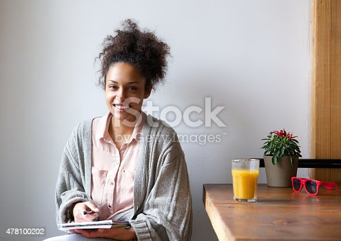 istock Smiling woman sitting at home with pen and paper 478100202