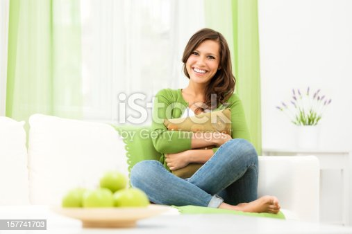 Smiling woman sitting confidently on a couch at home
