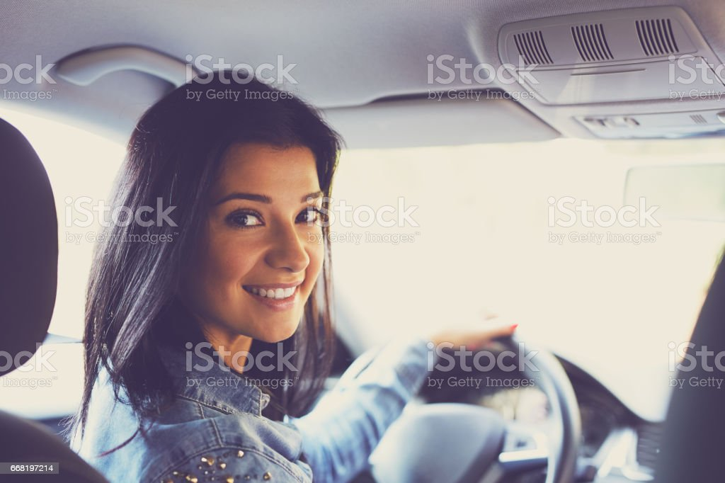 Smiling woman sitting in a car stock photo