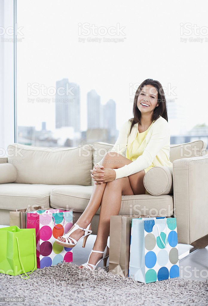 Smiling woman sitting in living room with shopping bags royalty-free stock photo