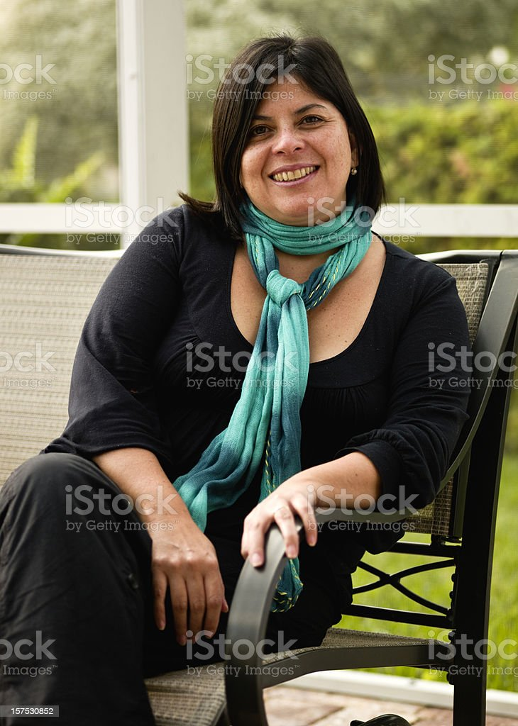 Smiling woman sitting in the backyard royalty-free stock photo