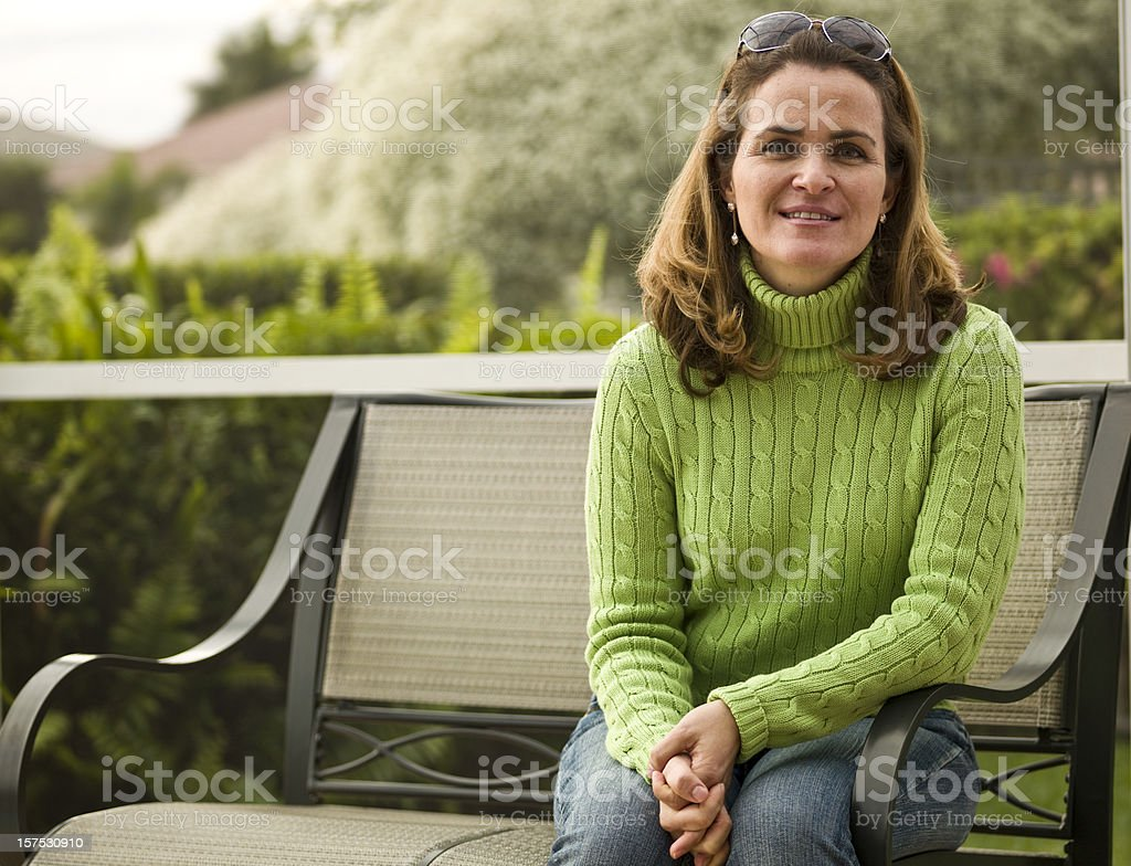 Smiling woman sitting in the backyard stock photo