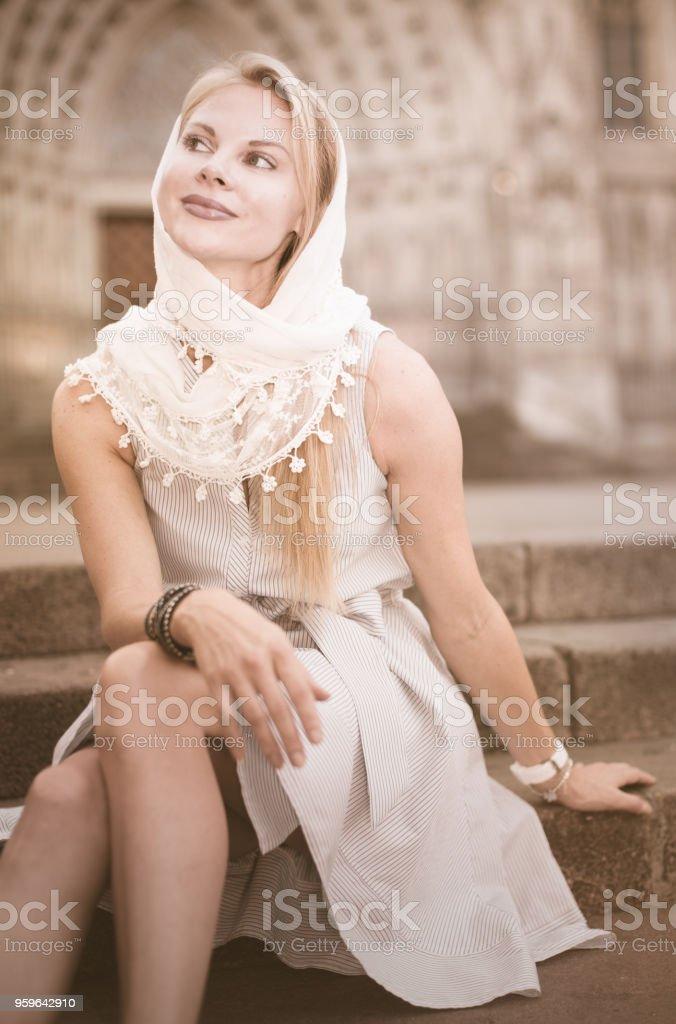mujer sonriente sentada en el centro de la ciudad en chal - Foto de stock de Adulto libre de derechos