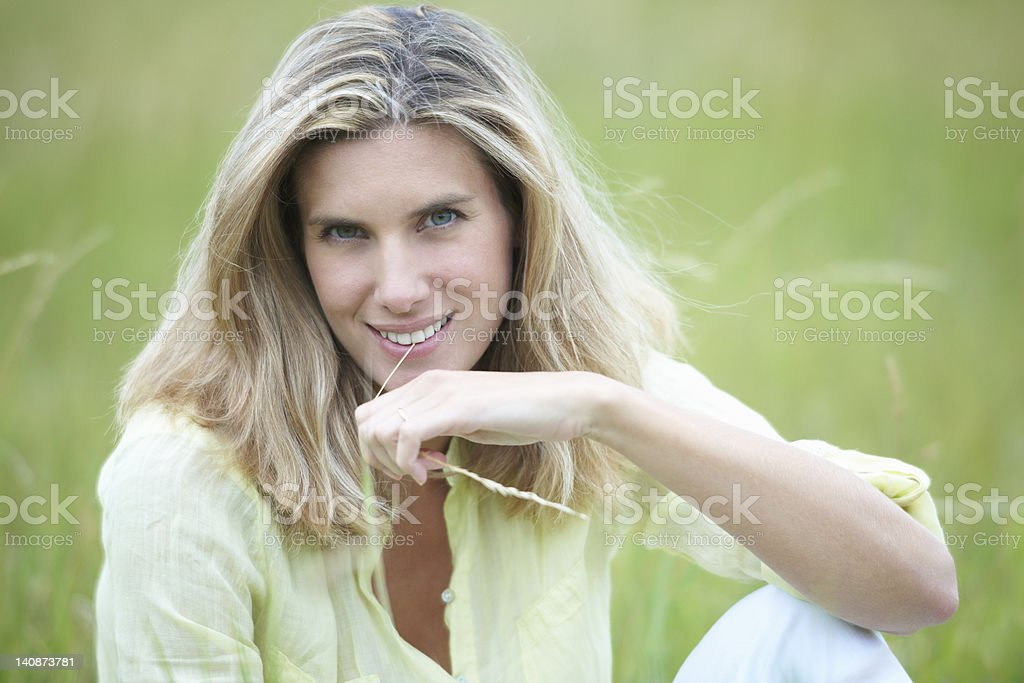 Smiling woman sitting in wheat field royalty-free stock photo