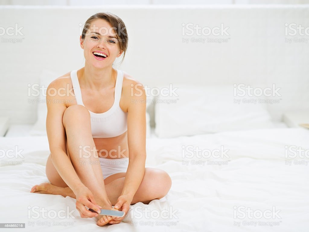 smiling woman sitting on bed and making manicure stock photo