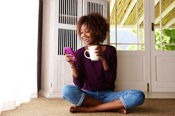 smiling woman sitting on floor at home with cell phone - sitting on floor stock photos and pictures