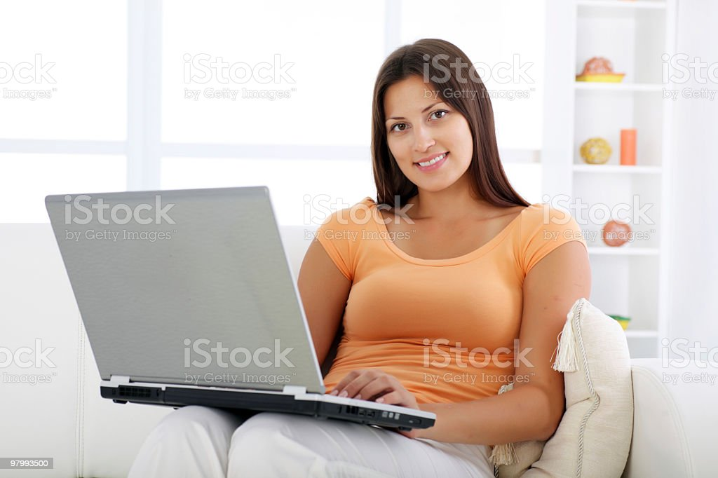 Smiling woman sitting on sofa with laptop. royalty-free stock photo