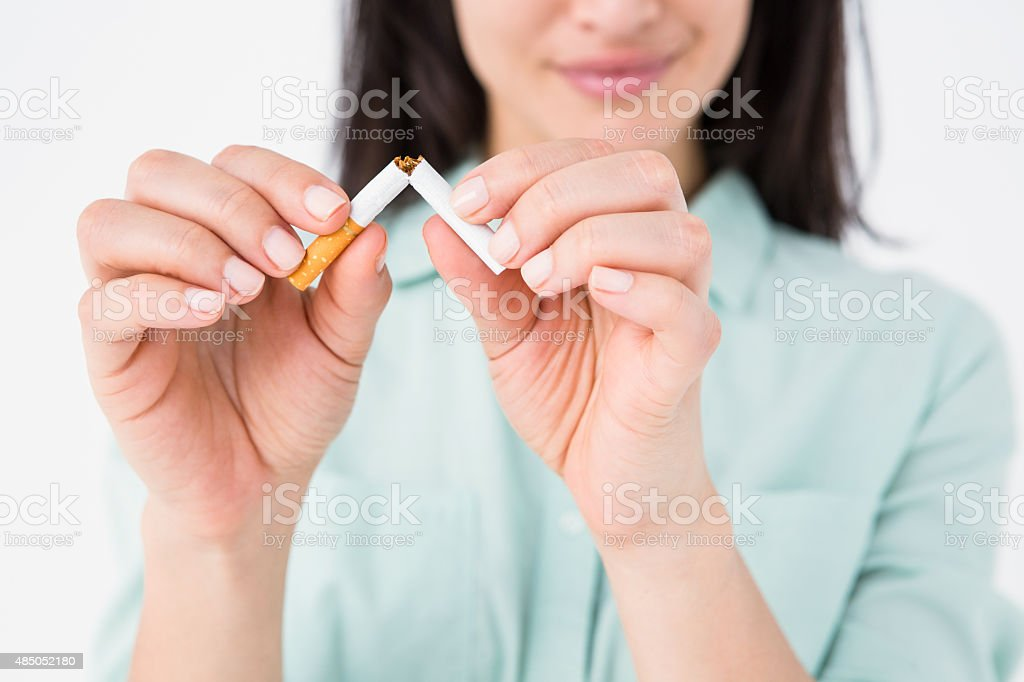 Smiling woman snapping cigarette in half stock photo