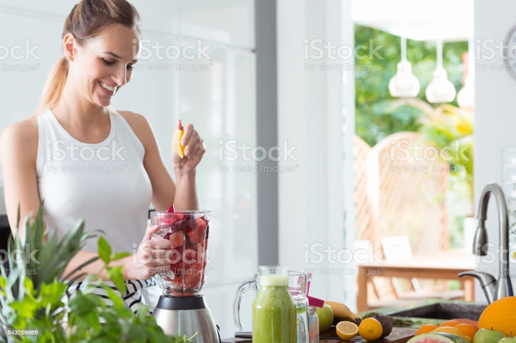 Smiling woman squeezing orange juice stock photo