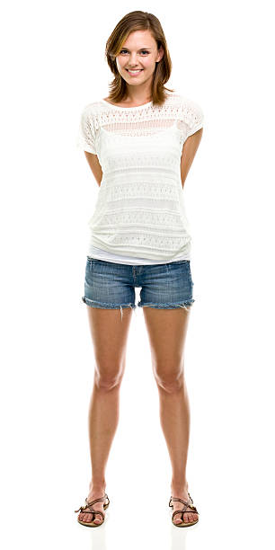 a smiling woman, standing against a white background  - jean shorts stock photos and pictures